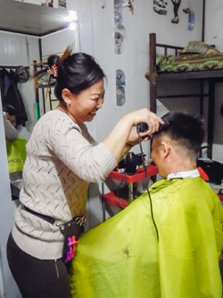A Mongolian assistant accountant runs a makeshift barbershop in the workers' dormitory in her spare time, Mongolia (Ruiyi Zhu, 2017)