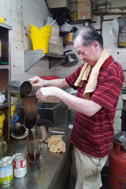 Ting, aged 65 years, strains coffee through a sieve in the back kitchen of a kopitiam (Helen Jambunathan, 2017)