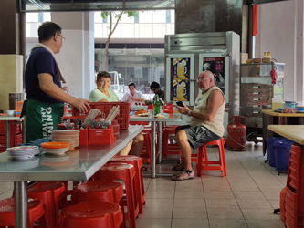Mr Tay, on the left, interacts with a British tourist couple in his kopitiam (Helen Jambunathan, 2017)