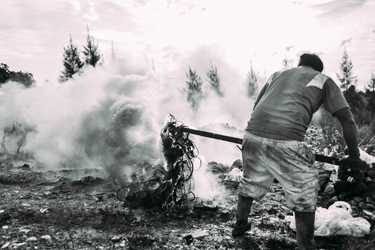 My neighbor Juan extracts copper by burning plastic cables recovered from the dump, while his son watches on (Patrick O'Hare, 2015)