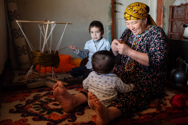 Entertaining the youngest grandson while her granddaughter helps spool synthetic yarn for alaja - colorful braids sold to city folks to adorn cars in the bridal party (Cara Kerven, 2016)